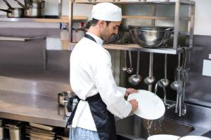 Foodservice-feature image of a man cleaning dishes in a industrial restaurante.